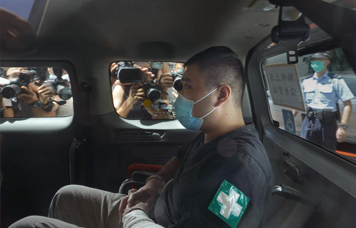 """File- In this Monday, July 6, 2020, file photo, Tong Ying-kit, 23 years old, arrives at a court for the violation of the new security law after carrying a flag reading """"Liberate Hong Kong, Revolution of our times"""" during a protest in Hong Kong. Tong has been sentenced to nine years in prison in the closely watched first case under Hong Kong's national security law as Beijing tightens control over the territory. (AP Photo/Vincent Yu, File)"""