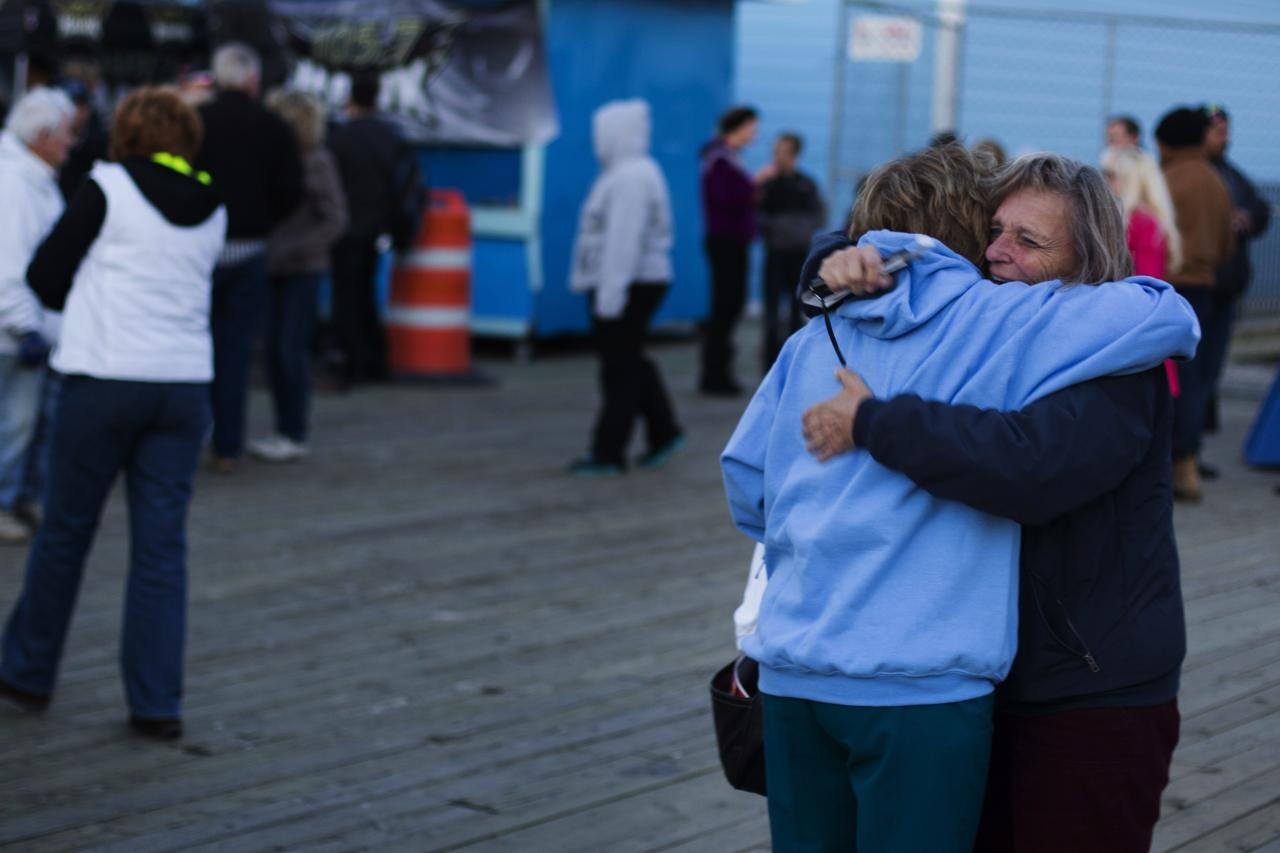 "Women seeing each other for the first time in a year greet while taking part in a ""Light The Shore"" event on the one year anniversary of the landfall of Hurricane Sandy in Seaside Heights, New Jersey October 29, 2013. A year after Superstorm Sandy inundated the East Coast with record flooding that left 159 people dead, residents of hard-hit New Jersey and New York shore communities still have a ways to go in rebuilding damaged homes. REUTERS/Lucas Jackson (UNITED STATES - Tags: DISASTER ENVIRONMENT ANNIVERSARY)"