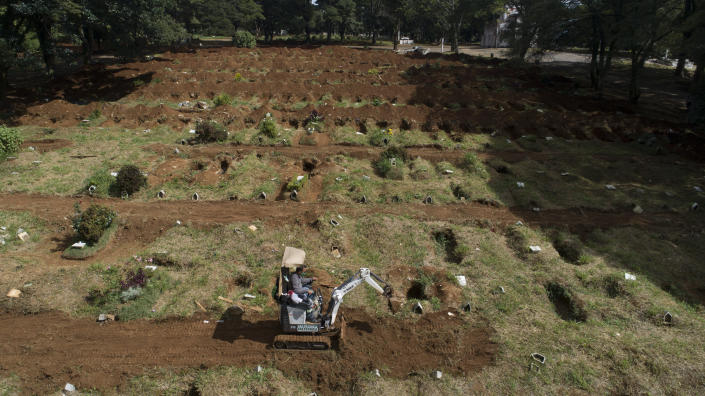 A worker digs more graves at the Vila Formosa cemetery amid the COVID-19 pandemic in Sao Paulo, Brazil, Wednesday, April 7, 2021. (AP Photo/Andre Penner)