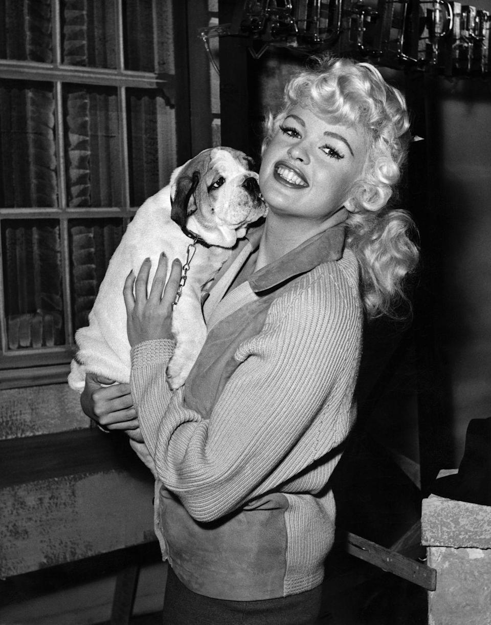 <p>Jayne Mansfield smiles with her five-month-old bulldog, Challenge, on the set of her movie <em>The Challenge</em>. The American bombshell, who was in England for a few months shooting the film, was given the puppy as a gift by an admirer. </p>
