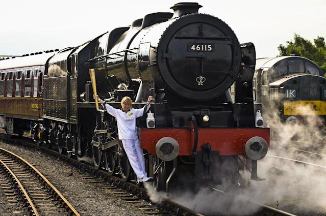 This image made available by LOCOG showsTorchbearer 004 Josephine Loughran carrying the Olympic Flame on the Scots Guardsman steam locomotive as they make the journey from York to Thirsk in England on day 33 of the torch relay Wednesday June 20, 2012. (P Photo/Ben Birchall, LOCOG, HO)