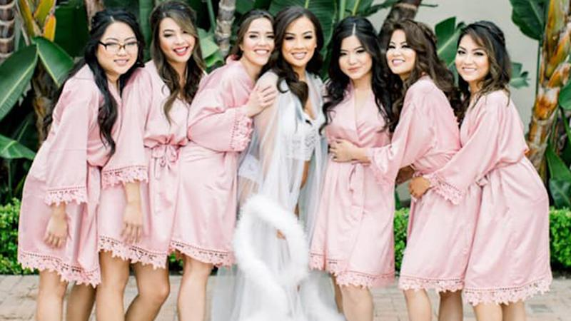 A photo of bride Victoria Vi Bass wearing white lingerie with her bridesmaids dressed in pink silky robes.