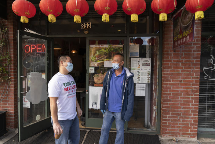 Benny Yun, owner of Yang Chow restaurant, left, talks to a fellow cafe owner Michael H., in Los Angeles, Thursday, Dec. 17, 2020. Bigotry toward Asian Americans and Asian food has spread steadily alongside the coronavirus in the United States. Yun said even though his businesses have survived the pandemic, they get prank calls almost daily asking if they have dog or cat on the menu or impersonating a thick Asian accent. (AP Photo/Damian Dovarganes)