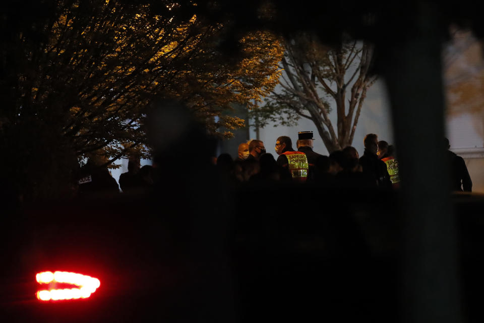 French rescue workers and police officers gather outside a high school after a history teacher who opened a discussion with students on caricatures of Islam's Prophet Muhammad was beheaded, Friday, Oct. 16, 2020 in Conflans-Sainte-Honorine, north of Paris. Police have shot the suspected killer dead. (AP Photo/Michel Euler)