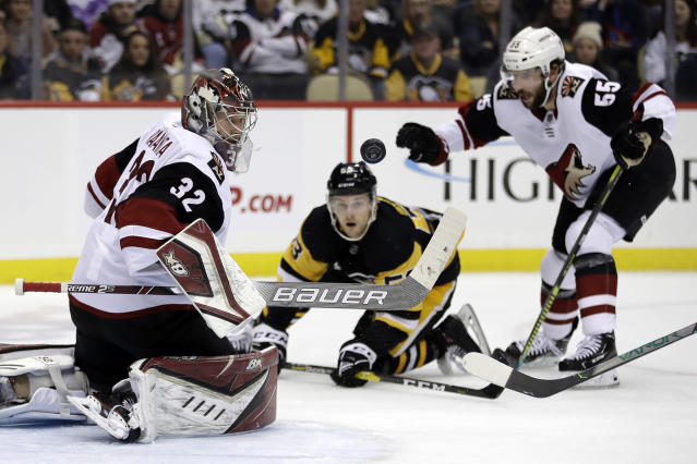 Arizona Coyotes goaltender Antti Raanta (32) stops a shot by Pittsburgh Penguins' Teddy Blueger (53) with Coyotes; Jason Demers (55) also defending during the second period of an NHL hockey game in Pittsburgh, Friday, Dec. 6, 2019. (AP Photo/Gene J. Puskar)