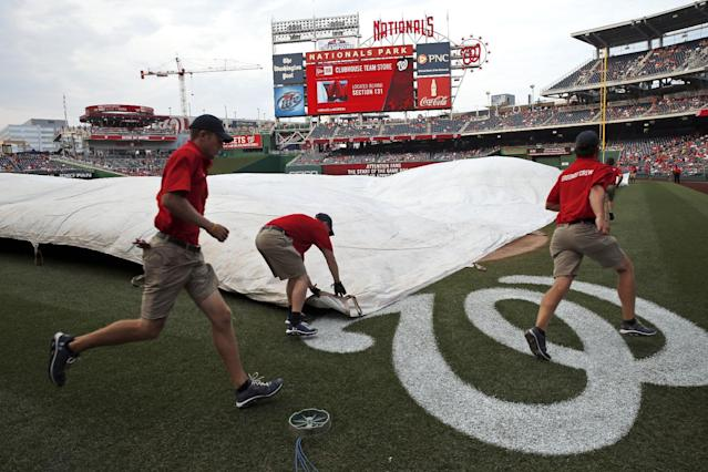 The Washington Nationals grounds crew works to cover the field before an interleague baseball game against the Baltimore Orioles at Nationals Park, Tuesday, July 8, 2014, in Washington. (AP Photo/Alex Brandon)