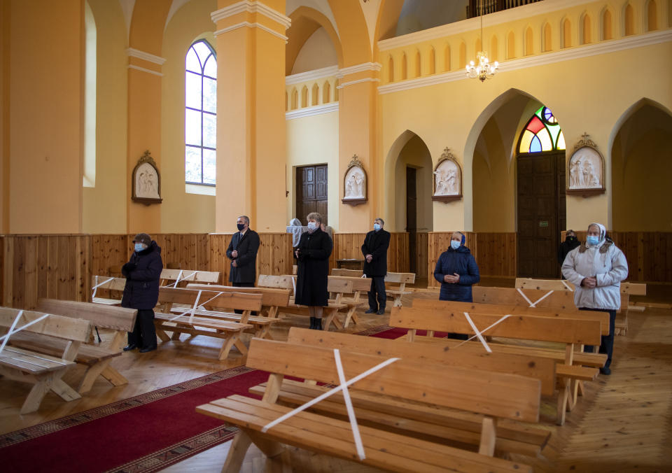 Worshippers wearing face masks and keeping social distance, pray during the Sunday Mass at the Church of Saint Stanislaus bishop in Kazitiskis, some 120km (74,5 miles) north of the capital Vilnius, Lithuania, on Sunday, Nov. 15, 2020. The entire country has been put under a three-week nationwide lockdown from Nov. 7 to Nov, 29, putting restrictions on social life and economic activities in order to stem the spread of the coronavirus, but churches are open for all worship. (AP Photo/Mindaugas Kulbis)
