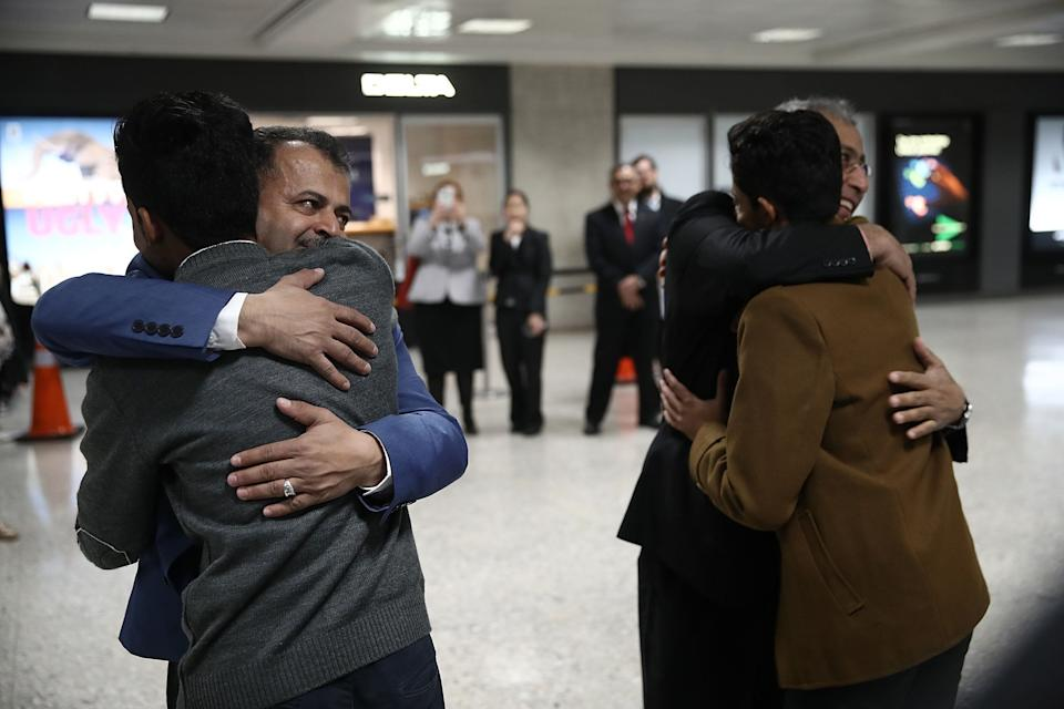Tareq Aquel Mohammed Aziz, left, hugs his father, Aquel, as his brother Ammar, second right, embraceshis uncle Jamil Assa after the brothers arrived from Yemen at Dulles International airport on Feb. 6, 2017.