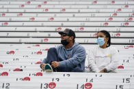 """Fans sit in the stands as rain delayed the start of the final practice session for the Indianapolis 500 auto race at Indianapolis Motor Speedway in Indianapolis, Friday, May 28, 2021. Seats are marked """"Do Not Use"""" to encourage social distancing. (AP Photo/Michael Conroy)"""