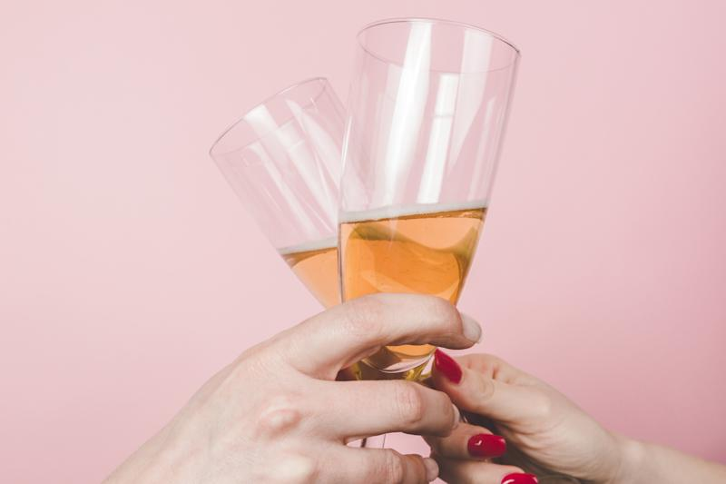 A close up of two women toasting with champagne glasses.