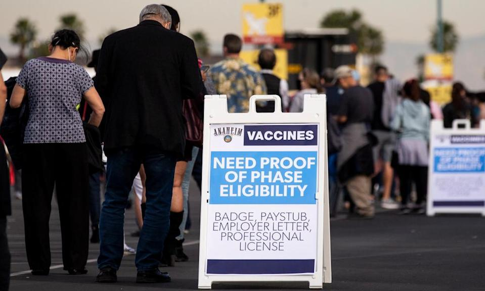 People queue as they wait to get vaccinated against Covid-19 in a parking lot at Disneyland in Anaheim, California.