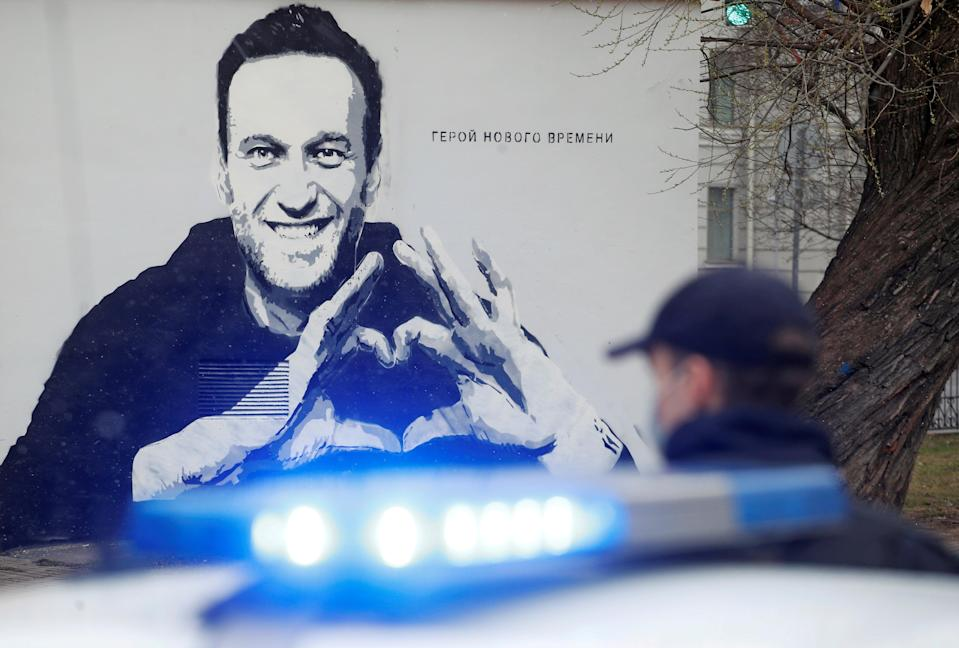 A police officer stands next to a car in front of graffiti depicting Alexei Navalny, with the words 'The hero of the new age', in Saint PetersburgReuters