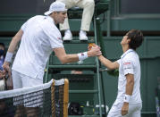 Japan's Yoshihito Nishioka shakes hands with John Isner of the United States after his win during the men's singles first round match on day three of the Wimbledon Tennis Championships in London, Wednesday June 30, 2021. (Jonathan Nackstrand/Pool via AP)