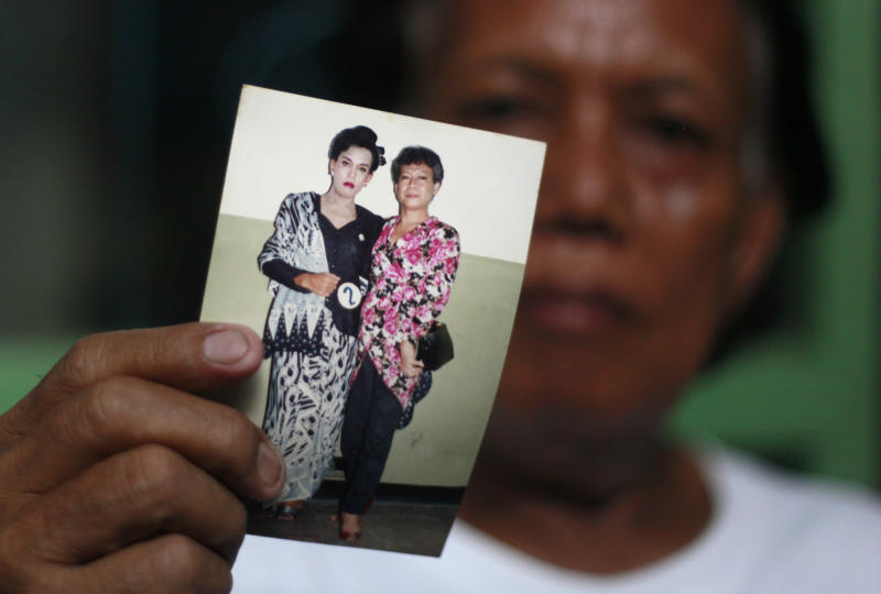 In this Friday, Jan. 27, 2012 photo, Evie, also known as Turdi, the former nanny of U.S. President Barack Obama, shows a picture of herself, left, dressed as a woman with an unidentified friend in a pageant, in Jakarta, Indonesia. Evie, who was born a man but believes she is really a woman, has endured a lifetime of taunts and beatings because of her identity. Nobody knows how many transgenders live in the sprawling archipelagic nation of 240 million, but activists estimate 7 million. However, societal disdain still runs deep - when transgenders act in TV comedies, they are invariably the brunt of the joke. (AP Photo/Dita Alangkara)
