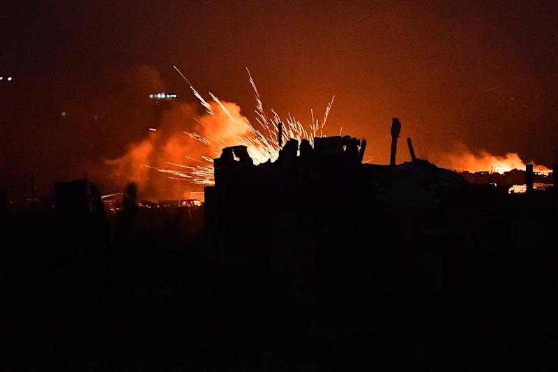 """Explosions rip though in the remains of the makeshift camp set up by diehard Islamic State State group fighters in the Syrian village of Baghouz for their """"caliphate's"""" doomed last stand (AFP Photo/GIUSEPPE CACACE)"""