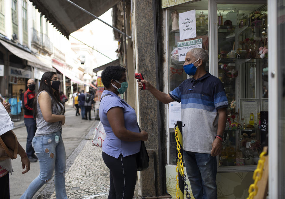 People line up to get their temperature checked before entering a store in downtown amid the new coronavirus pandemic in Rio de Janeiro, Brazil, Monday, June 29, 2020. Rio de Janeiro and Sao Paulo, the states with the highest number of COVID-19 victims and cases, continue to ease measures applied since March and the streets are filling up with people. (AP Photo/Silvia Izquierdo)