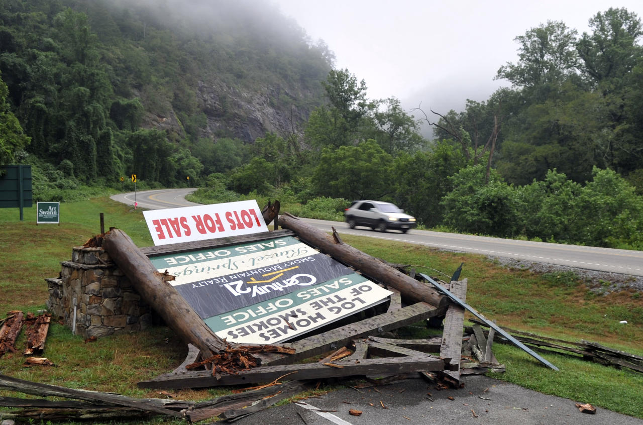 A sign advertising lots for sale lies in pieces on the ground in the Kinzel Springs community Friday, July 6, 2012, near Townsend, Tenn., following a violent storm that swept through nearby Great Smoky Mountains National Park Thursday evening, killing at least two park visitors and injuring others. (AP Photo/The Knoxville News Sentinel, J. Miles Cary)