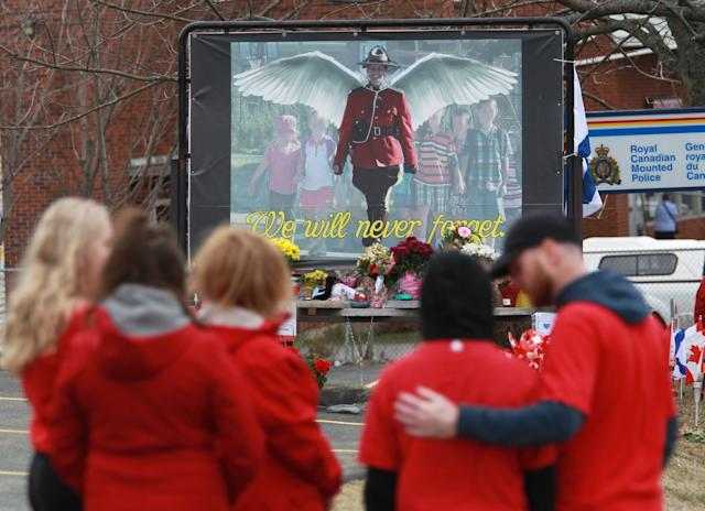 Mourners, asked to wear red, are seen near a mural dedicated to slain RCMP Const. Heidi Stevenson, during a province-wide, two-minutes of silence for the 22 victims of last weekend's shooting rampage, in front of the RCMP detachment in Cole Harbour, N.S. on April 24, 2020. (Photo: Tim Krochak/CP)