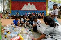About 65 kids are enrolled at the school, where classroom walls are made of painted car tyres and the entrance adorned with a mural of the Cambodian flag made entirely from colourful bottle caps