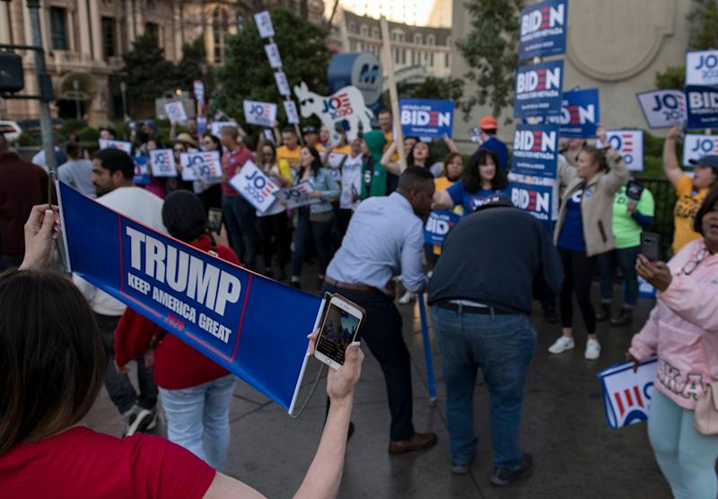 A supporter of Mr Trump with a placard outside the venue of the Democratic debate: Getty