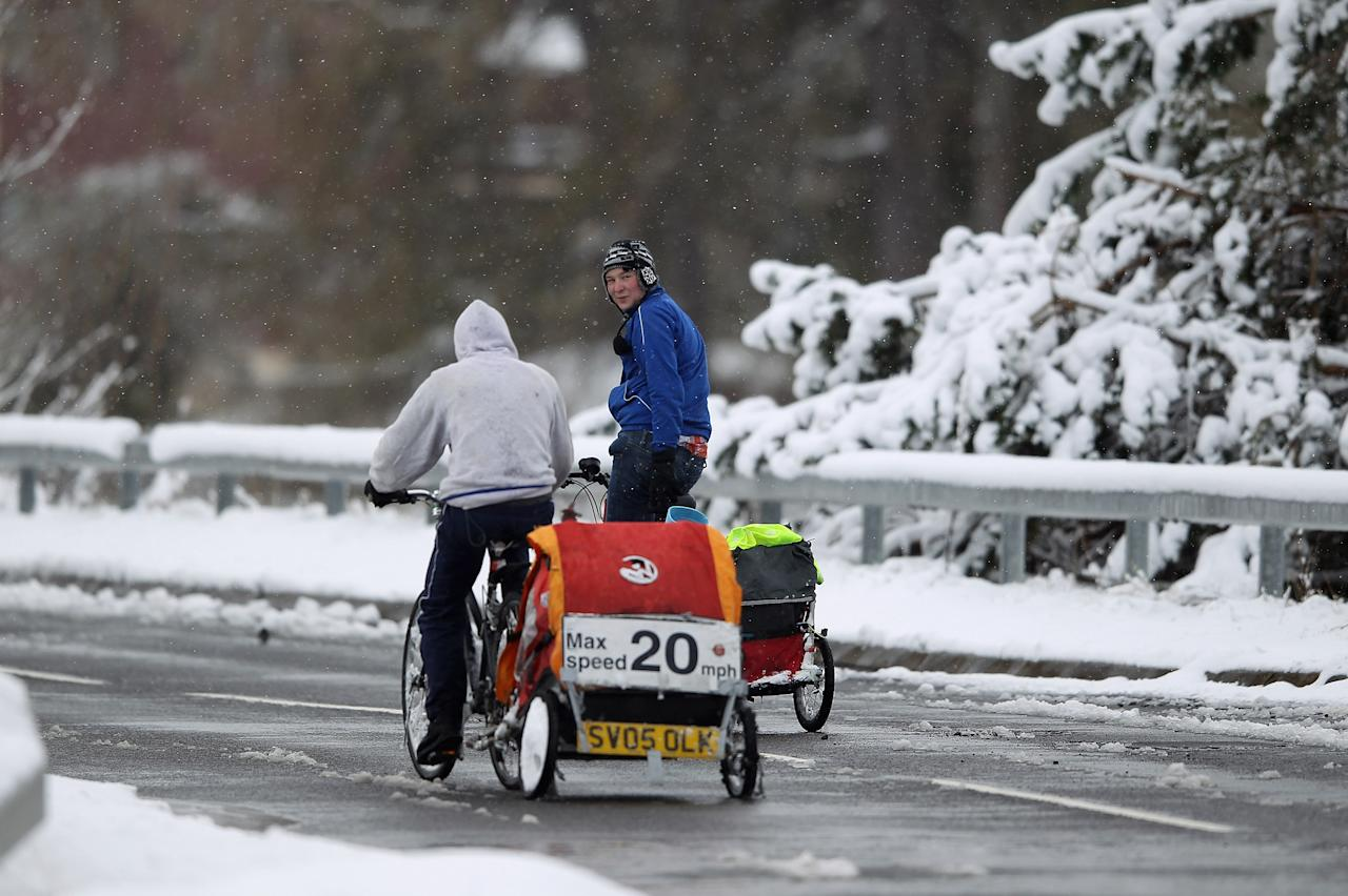 SPITTAL OF GLENSHEE, SCOTLAND - APRIL 03:  Two cyclists make their way along the A93 on April 3, 2012 in Spittal of Glenshee, Scotland. Snow has returned to parts of Scotland just a week after the country experienced record high temperatures for March. (Photo by Jeff J Mitchell/Getty Images)