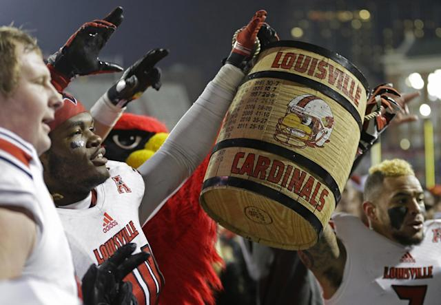 Louisville players hoist the Keg of Nails after they defeated Cincinnati 31-24 in overtime of an NCAA college football game on Thursday, Dec. 5, 2013, in Cincinnati. (AP Photo/Al Behrman)
