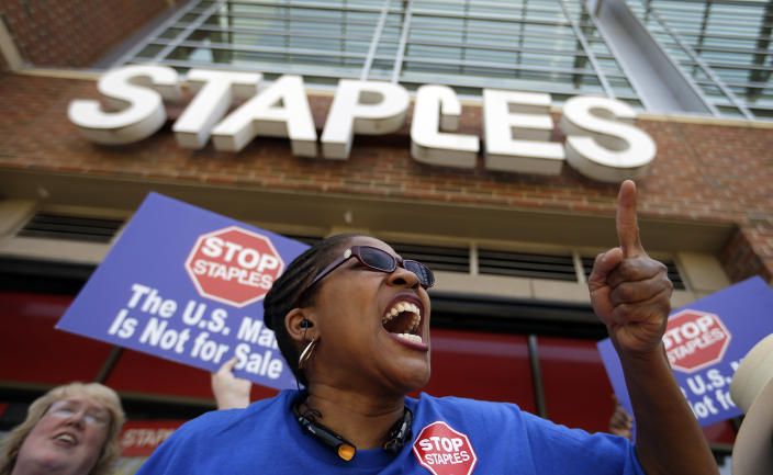 """U.S. Post Office employee Detra Parker chants during a protest outside a Staples store, Thursday, April 24, 2014, in Atlanta. Thousands of postal workers picketed outside Staples stores nationwide Thursday to protest a pilot program that allows the office supply chain to handle U.S. mail. The American Postal Workers Union fears layoffs and post office closings and says that unlike retail workers, postal workers """"have taken an oath to protect the sanctity of the mail."""" (AP Photo/David Goldman)"""