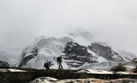 People walk near the Hualcan glacier in the Huascaran natural reserve in Ancash