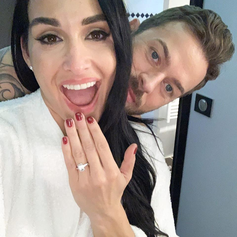 """<p>On New Year's Day, Nikki Bella and Artem Chigvintsev shared the news that they had been engaged for two months. The former WWE wrestler took to Instagram posting a photo of the romantic proposal in France—complete with red roses and string quartet—as well as a gorgeous emerald cut engagement ring. """"Excited for 2020 and the next decade with you @TheArtemC. I said yes in France in November! We have been trying to keep it a secret but really wanted to share our excitement for the New Year!"""" she captioned the pics.</p> <p>Chigvintsev, a <em>Dancing With the Stars</em> pro, also posted to social media, penning, """"You are the best thing that has ever happened to me. So excited for what's to come I love you more than anything and thank you for saying 'Yes.'""""</p> <p>The couple met in 2017 when they were partners for the 25th season of the dancing competition show. But they didn't begin dating until late 2018, after Bella had broken things off with her fiancé at the time, John Cena.</p>"""