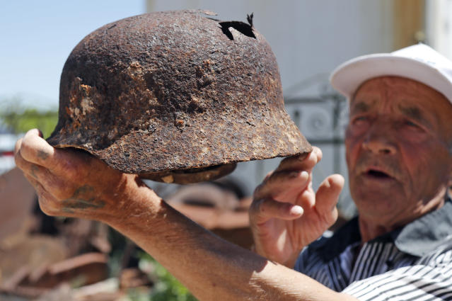 In this photo taken on Sunday, June 17, 2018, 72 year old Vitaly Danilkin holds up memorabilia and remains of battles that took place near Stalingrad, in Rossoshka, Russia. Vitaly Danilkin takes care for a cemetery some 40 miles northwest of Volgograd in Rossoshka, for German soldiers who perished at Stalingrad and nearby Rostov-on-Don, as well as a Soviet cemetery on the other side of the road. Nearly 60 years since it changed its name to Volgograd, the Russian city once called Stalingrad and its bloody history loom large even in the midst of the fun and football of the World Cup. (AP Photo/Frank Augstein)
