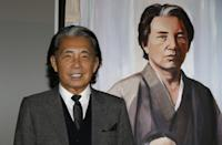 Japanese fashion designer Kenzo Takada poses next to his self-portrait painting during the Monaco Fight Aids Gala, on december 1, 2014 in Monaco, as part of the World AIDS Day. AFP PHOTO / VALERY HACHE ---RESTRICTED TO EDITORIAL USE, MANDATORY MENTION OF THE ARTIST UPON PUBLICATION, TO ILLUSTRATE THE EVENT AS SPECIFIED IN THE CAPTION--- (Photo credit should read VALERY HACHE/AFP via Getty Images)