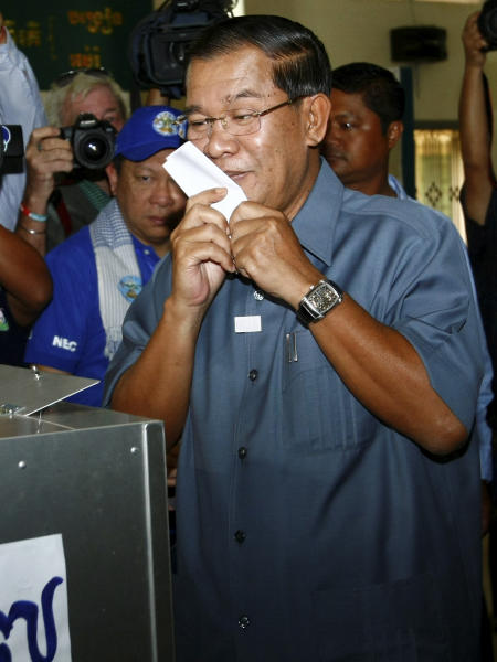 Cambodia's Prime Minister Hun Sen kisses his ballot at a polling station in Takhmau town, south of Phnom Penh, Cambodia, Sunday, July 28, 2013. Hun Sen was among the early voters Sunday, casting his ballot shortly after the polls opened in a national election his party is expected to easily dominate. (AP Photo/Heng Sinith)