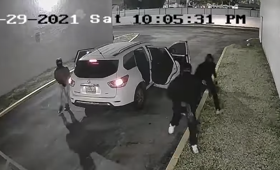 A CCTV still of the three suspects of a Miami birthday party concert shooting leaving a white SUV, carrying guns.
