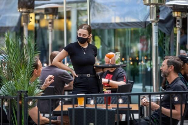 A server takes an order from patrons at a restaurant in downtown Vancouver, British Columbia on Tuesday, June 22, 2021.  (Ben Nelms/CBC - image credit)