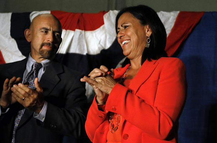 Democratic state Sen. Angela Giron, right, with Colorado Lt. Gov. Joseph Garcia standing beside her, smiles as she greets a crowd of supporters at a rally on the night in which the tally of a close recall vote were still being counted, in Pueblo, Colo., Tuesday Sept. 10, 2013. Campaigns worked to get as many voters as possible to the polls in Colorado's first legislative recalls on Tuesday, elections that tested popular support for gun limits in a state with a strong tradition embracing Second Amendment rights. (AP Photo/Brennan Linsley)