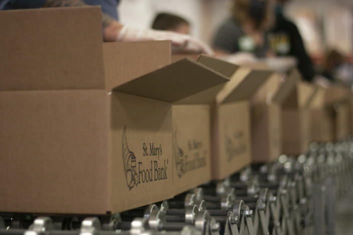 Volunteers at St. Mary's Food Bank in Phoenix fill boxes with peas, beans, grains and canned foods to be distributed to families in need on Thursday, March 18, 2021. The group, which includes 30 families, is expected to package about 1,500 boxes in two hours. (AP Photo/Cheyanne Mumphrey)