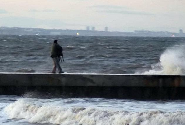 This is the shocking a moment a heartless dog owner appears to throw his terrified greyhound into the freezing ocean.