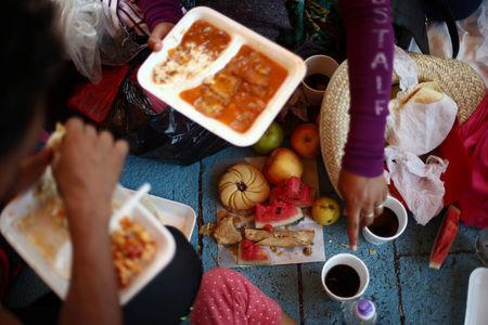Central American migrants, moving in a caravan through Mexico toward the U.S. border, eat at a shelter set up for them by the Catholic church, in Puebla, Mexico April 6, 2018. REUTERS/Edgard Garrido