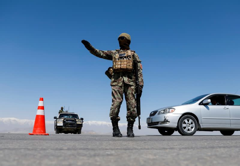 FILE PHOTO: An Afghan National Army soldier stands guard at a checkpoint on the outskirts of Kabul