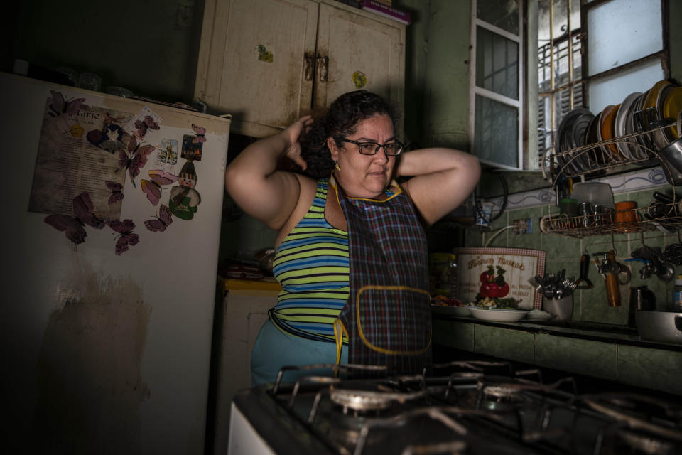 """Yuliet Colon puts on her apron as she prepares to cook a dish in her kitchen in Havana, Cuba, Friday, April 2, 2021. Colon found for herself and many Cubans a solution that combines ingenuity with the innovative use of the Internet on the island and became a contributor to the Facebook page """"Recipes from the Heart,"""" with tips, ideas and tricks to get ahead with what items are actually available at the market. (AP Photo/Ramon Espinosa)"""
