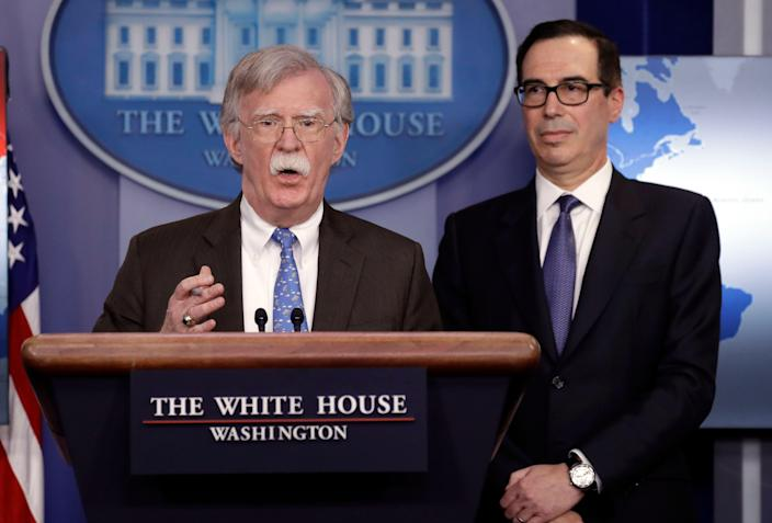 National security adviser John Bolton speaks as Treasury Secretary Steven Mnuchin listens during a press briefing at the White House, Monday, Jan. 28, 2019, in Washington.