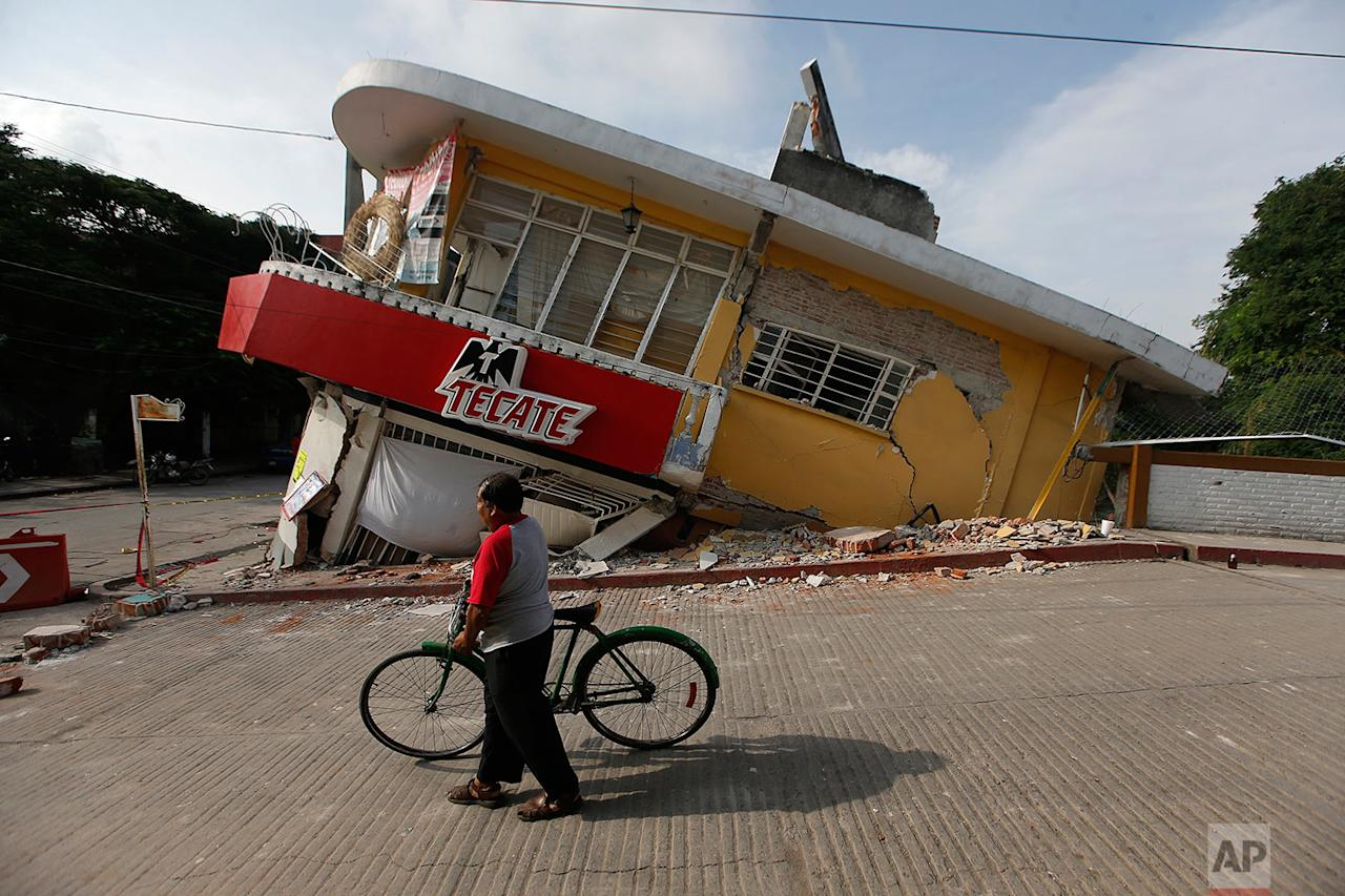 <p>A man walks his bike past a building felled by a 7.1 earthquake, in Jojutla, Morelos state, Mexico. Buildings collapsed in Morelos state, including the town hall and local church in Jojutla near the quake's epicenter. (AP Photo/Eduardo Verdugo) </p>