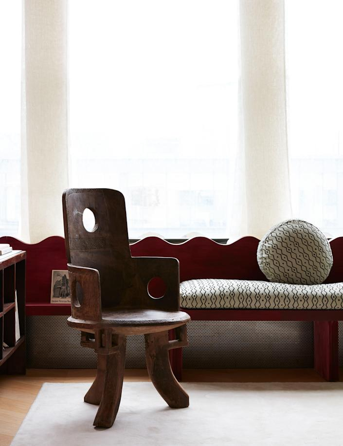 In the living room, Valle designed a low wood screen along the window wall that turns into a window seat. The wood is stained a rich red; the fabric on the cushions is from Le Manach.