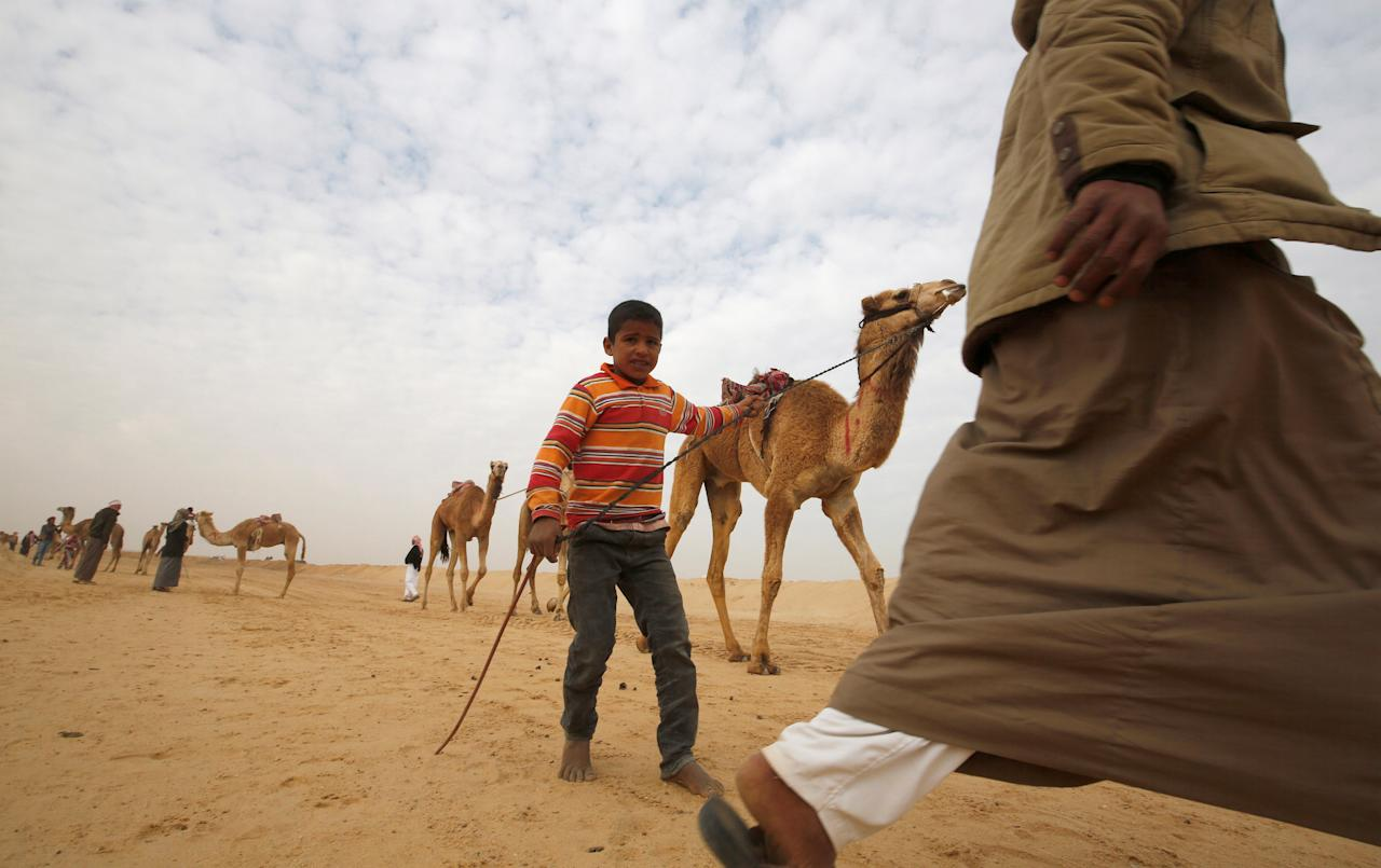 Hashem, an 8-year-old jockey, looks on during the opening of the International Camel Racing festival at the Sarabium desert in Ismailia, Egypt, March 21, 2017. Picture taken March 21, 2017. REUTERS/Amr Abdallah Dalsh