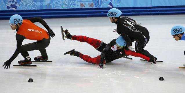 Canada's Charles Hamelin (2nd L) crashes into Eduardo Alvarez of the U.S. during the men's 1,000 metres short track speed skating quarter-finals race at the Iceberg Skating Palace at the Sochi 2014 Winter Olympic Games February 15, 2014. REUTERS/Eric Gaillard (RUSSIA - Tags: OLYMPICS SPORT SPEED SKATING)