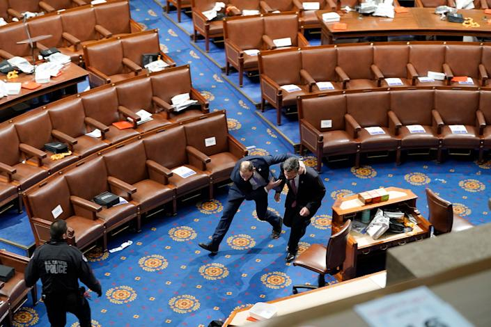 """Members of Congress run for cover as pro-Trump rioters try to enter the House Chamber.<span class=""""copyright"""">Drew Angerer—Getty Images</span>"""