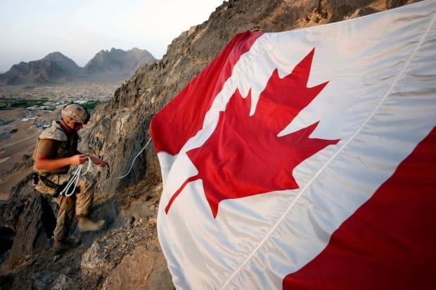 Canadian soldier Jeff Wright marks Canada Day by hanging the flag on a mountainside above the forward operating base of Ma'sum Ghar on July 1, 2007. (Finbarr O'Reilly/Reuters - image credit)