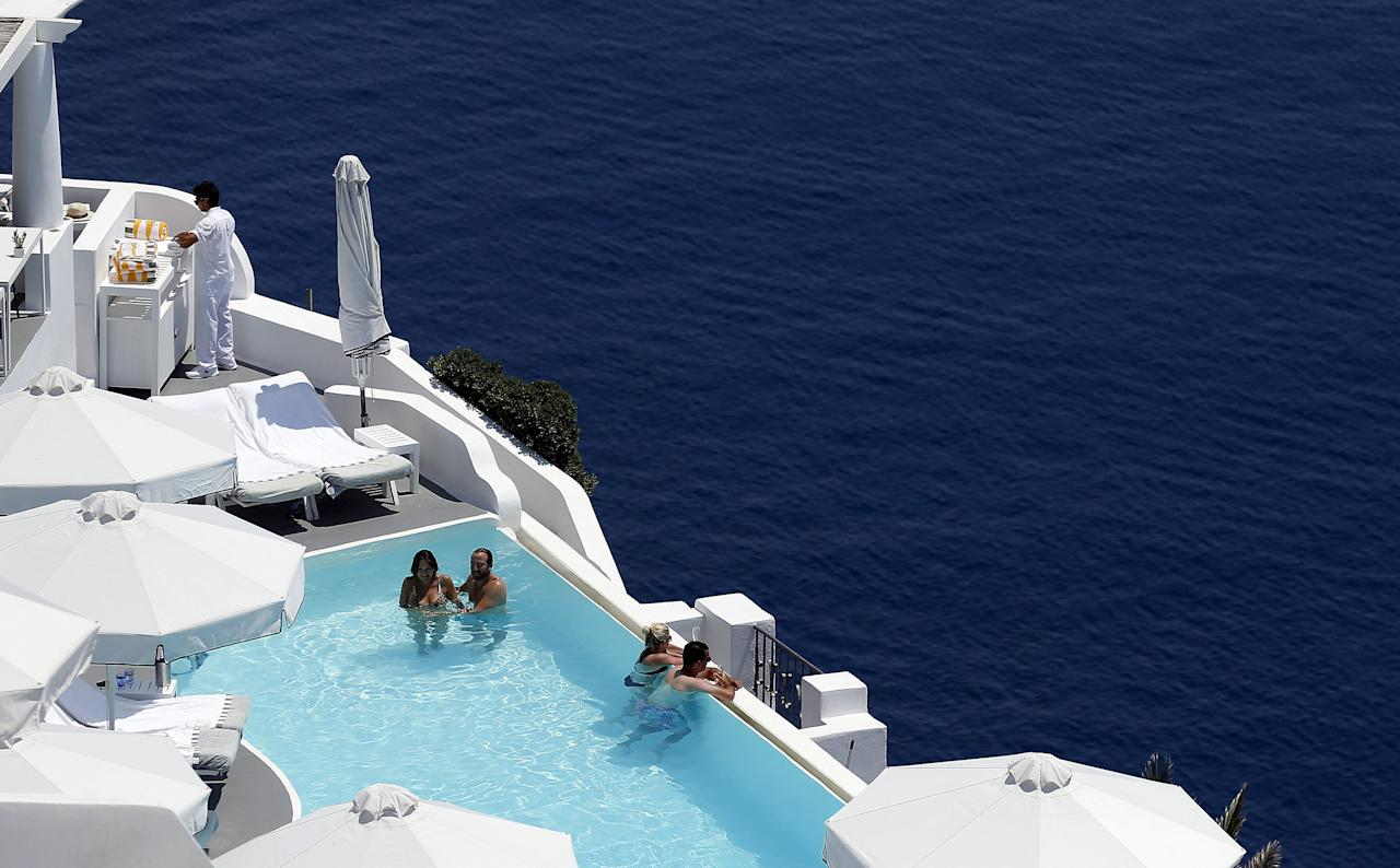 Tourists relax in a private swimming pool in the village of Oia on the Greek island of Santorini, Greece, July 1, 2015. REUTERS/Cathal McNaughton/Files