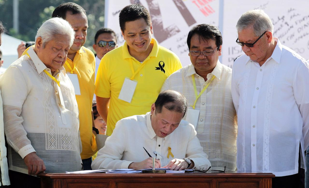 Philippine President Benigno Aquino III signs the Human Rights Victims Reparation and Recognition Act of 2013 during the 27th anniversary of EDSA 1 People Power Revolution in Quezon City, north of Manila on 25 February 2013. EDSA People Power Revolution also known as the EDSA Revolution, or People Power) was a four-day series of non-violent mass demonstrations that toppled the Marcos dictatorship and installed Corazon Aquino as president in 1986. (Czeasar Dancel/NPPA Images)