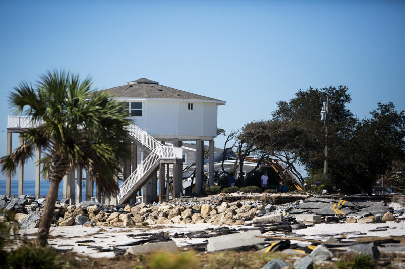 Residents assess the damage to their home after Hurricane Michael hit Alligator Drive in Alligator Point, Fla., on Friday, Oct. 12, 2018. (Tailyr Irvine/The Tampa Bay Times via AP)